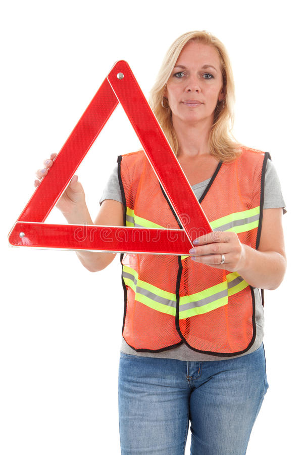 Woman in safety vest. Holding foldaway reflective road hazard warning triangle over white background stock image