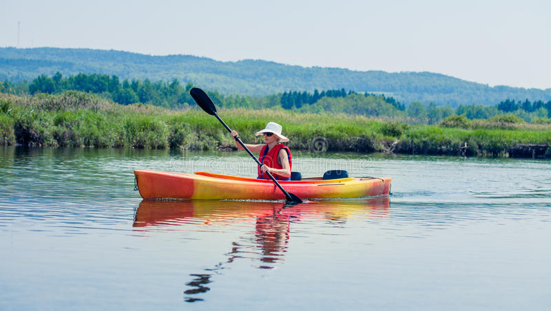 Woman With Safety Vest Kayaking Alone on a Calm River royalty free stock photography