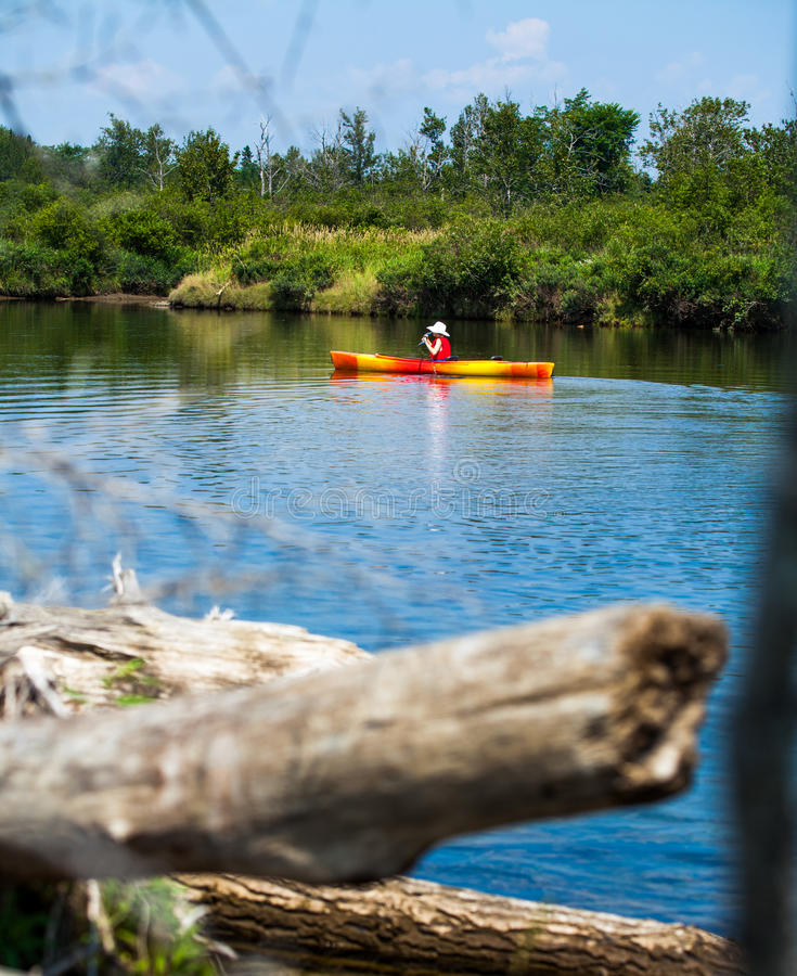 Woman With Safety Vest Kayaking Alone on a Calm River stock photo