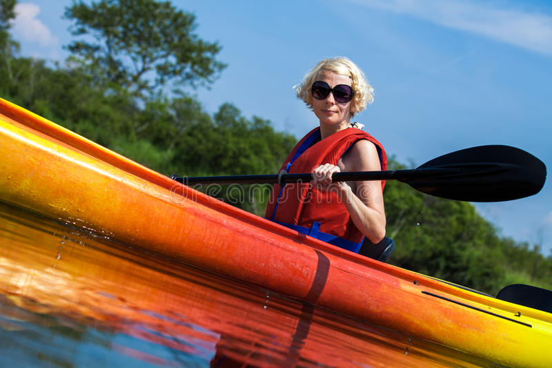 Woman With Safety Vest Kayaking Alone on a Calm River. Young Woman Kayaking Alone on a Calm River and Wearing a Safety Vest stock photos