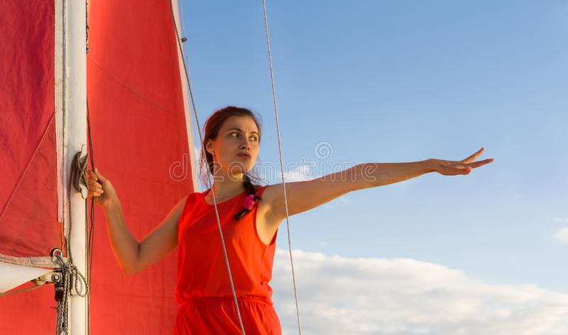 Woman on the sailboat points forward stock photo