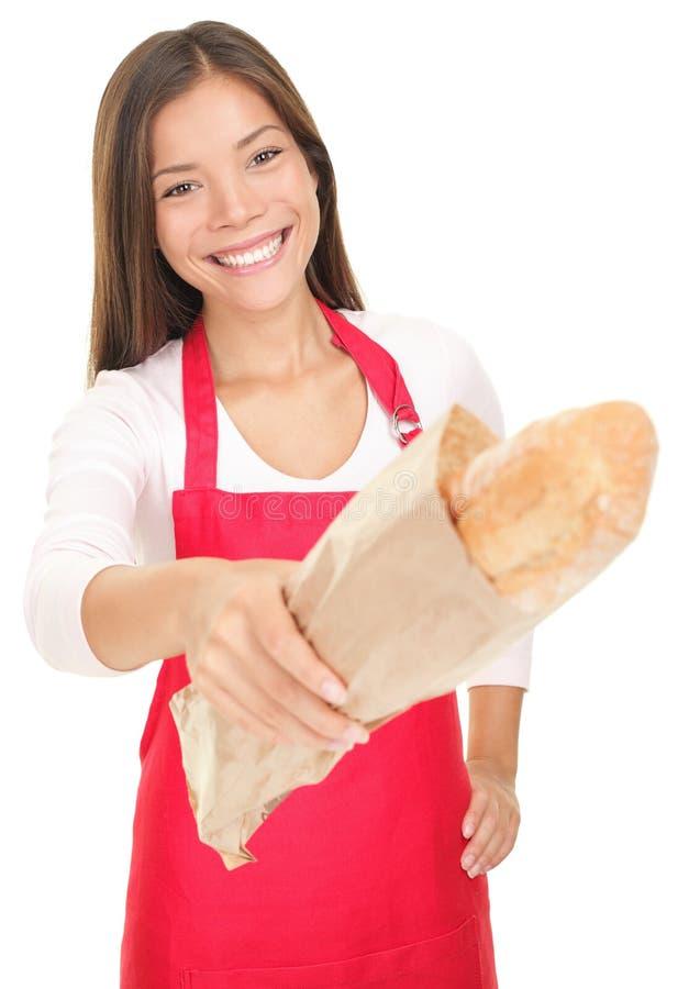 Woman sales clerk giving bread stock image