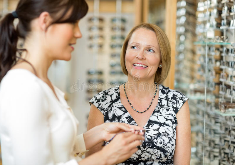 Woman With Salesgirl Selecting Glasses In Store. Happy senior women with salesgirl selecting glasses in optician store stock images