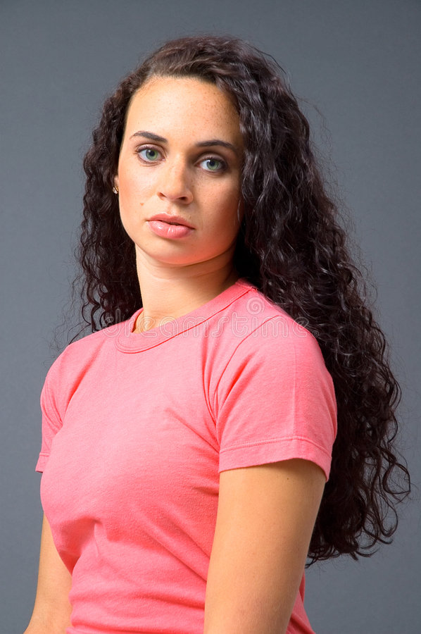 Woman in Salmon colored Shirt. A headshot of a beautiful woman with brilliant green eyes and long, dark curly hair, in a salmon-colored shirt on a neutral grey royalty free stock images