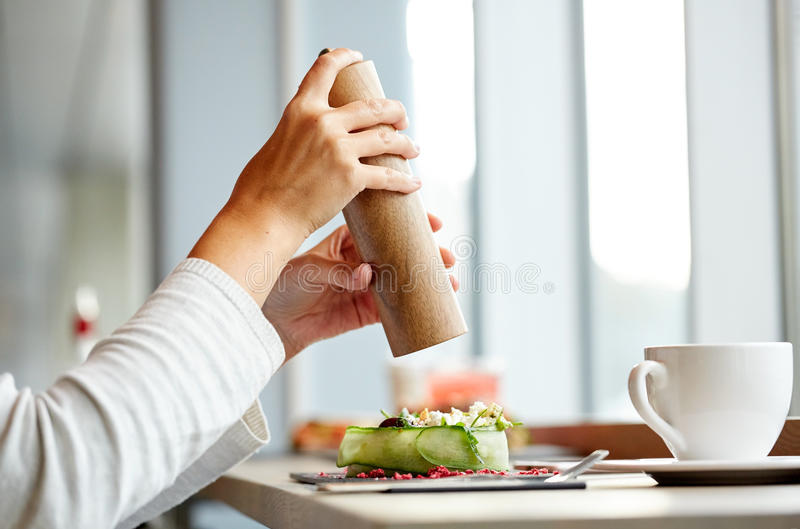 Woman with salt shaker and salad at restaurant royalty free stock photo