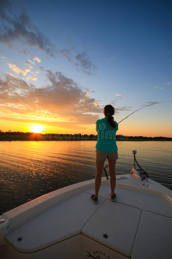Woman Saltwater Fishing Casting From Boat During Sunrise royalty free stock photo