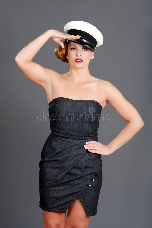 Woman saluting. Portrait of a woman saluting with hat on gray background royalty free stock photos