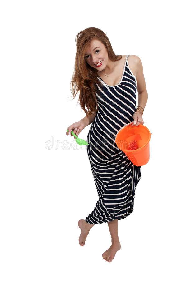 Woman with a sand pail. Beautiful young woman holding a sand pail and a toy shovel stock images