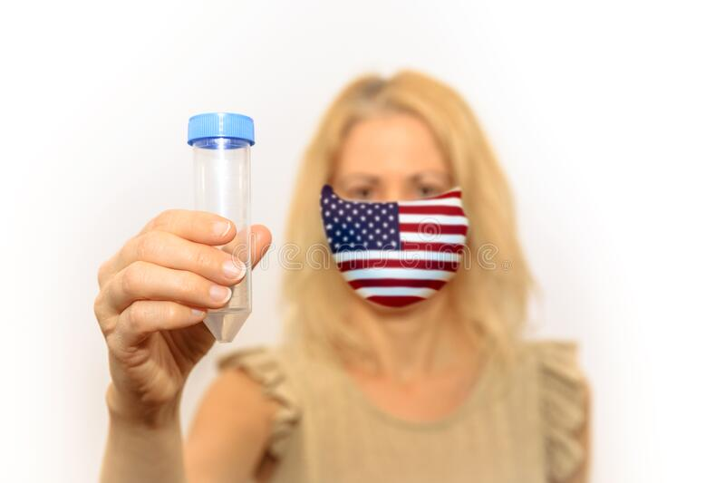 Woman with sanitary mask in United States. Woman with American flag face mask holding a test tube. Concept of the outbreak and quarantine for infection of the royalty free stock images