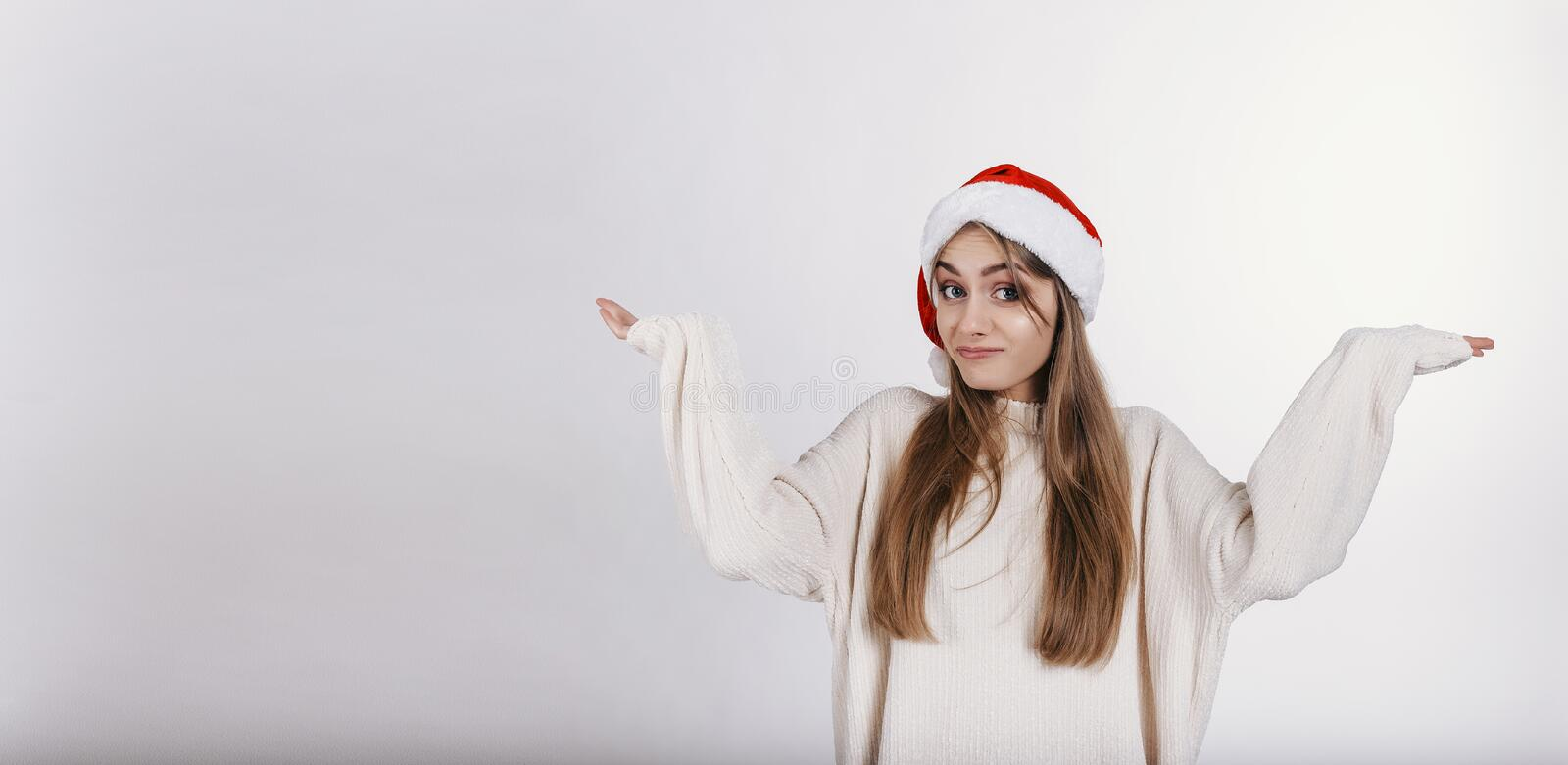 Woman in santa claus hat spread wide her hands and looking at camera with anxious royalty free stock photography