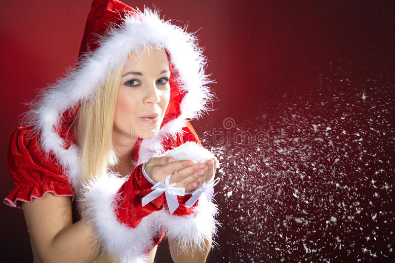 Woman with santa hat blows the snow stock photos