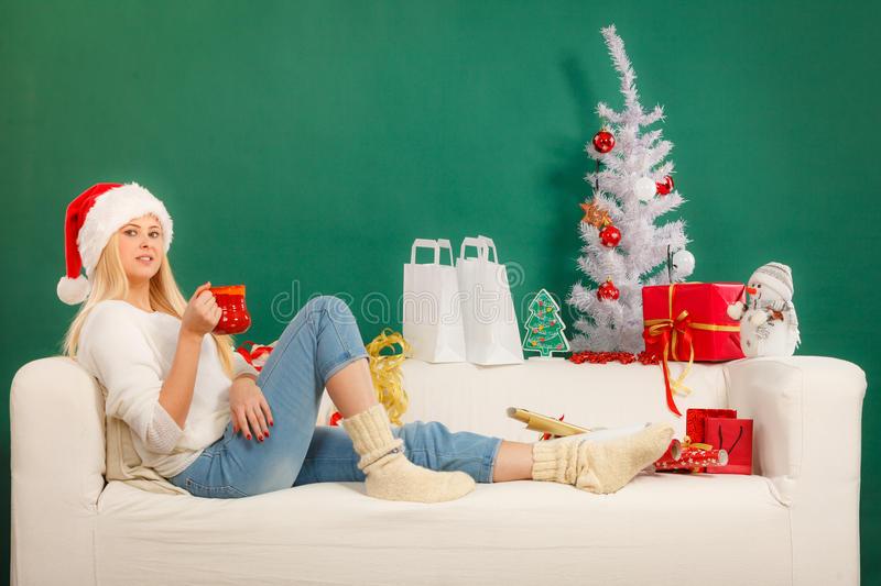 Woman in santa hat drinking from mug royalty free stock photo