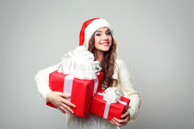 Woman in santa hat with gift boxes stock photography