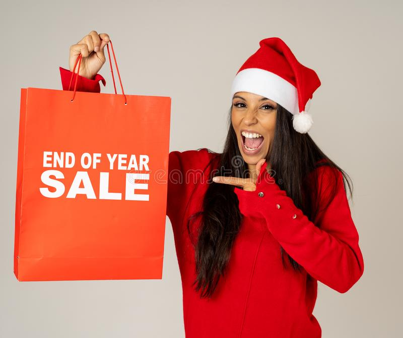 Woman in Santa hat holding christmas shopping bag with Sales written on it looking excited and happy royalty free stock photography