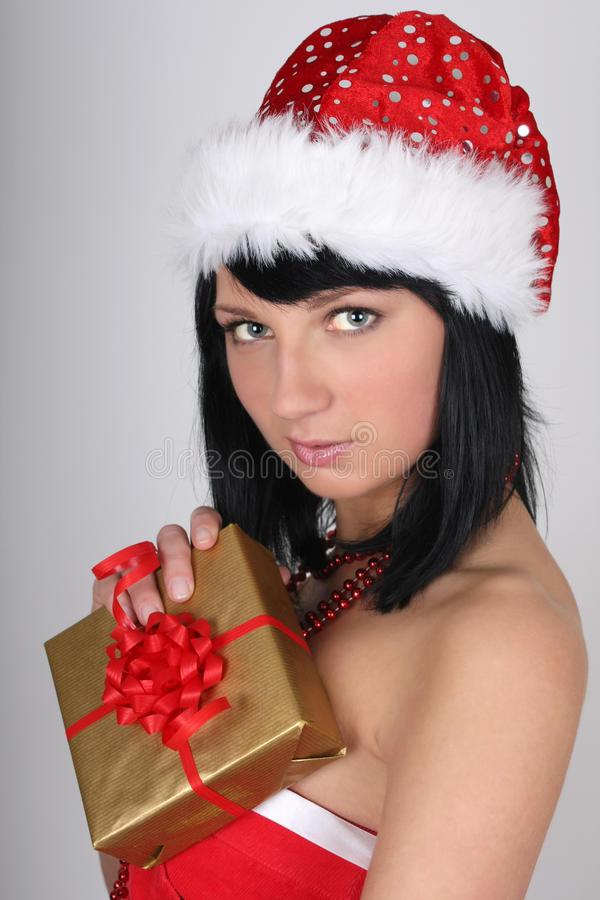 Download Woman In Santa Hat Holding Golden Present Stock Photo - Image: 17107008