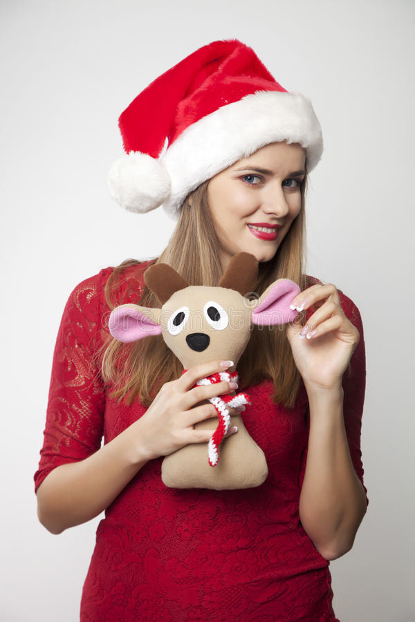 Woman in Santa Hat. Holding reindeer toy royalty free stock photos