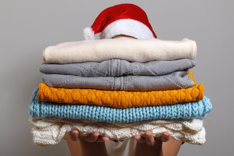 Woman in santa hat holding a stack of warm knitted sweaters on a gray wall background. Winter and christmas concept. royalty free stock photos