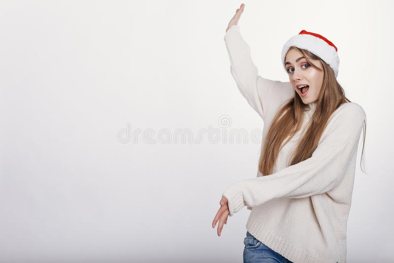 Woman in santa hat pointing on somthing big stock photo