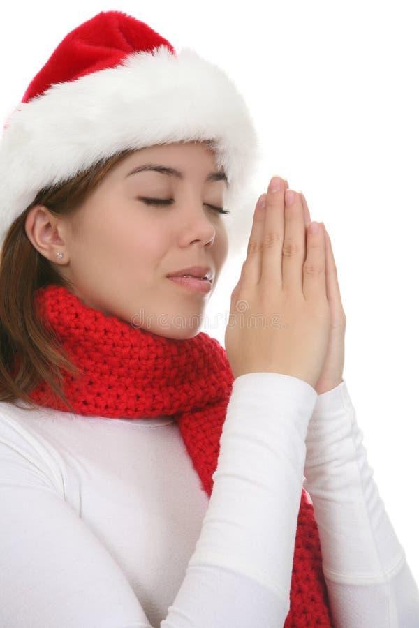 Woman in Santa hat praying stock image