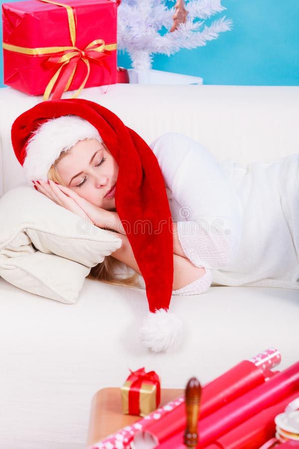 Woman in Santa hat sleeping on couch stock images