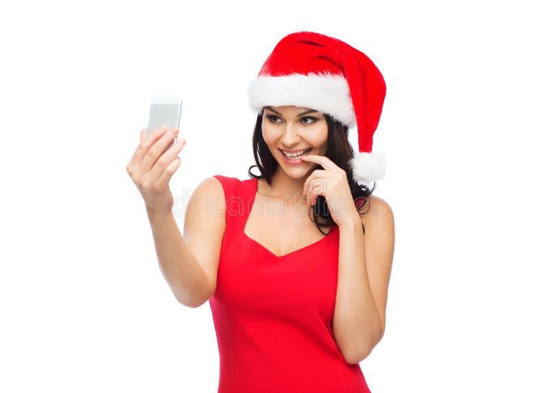 Woman in santa hat taking selfie by smartphone royalty free stock image