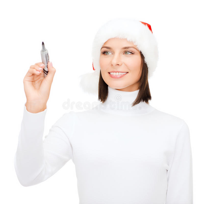 Woman in santa helper hat drawing or writing. Christmas, x-mas, winter, happiness concept - smiling woman in santa helper hat drawing or writing something in the royalty free stock photos