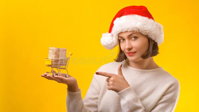 Woman Santa helper holding shopping cart. Small cart with money for christmas gifts. Christmas shopping and sales. New Year royalty free stock photos
