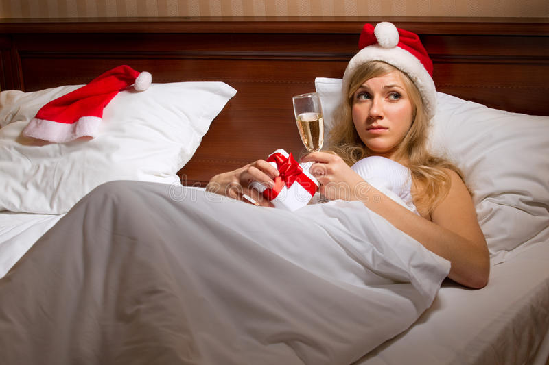Woman in Santa's hats remain all alone. Young woman in Santa's hats with glass of champagne lying on bed remain all alone stock photography