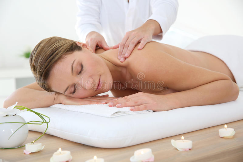 Woman in sapa getting a massage. Woman in spa institute receiving oil massage stock photo