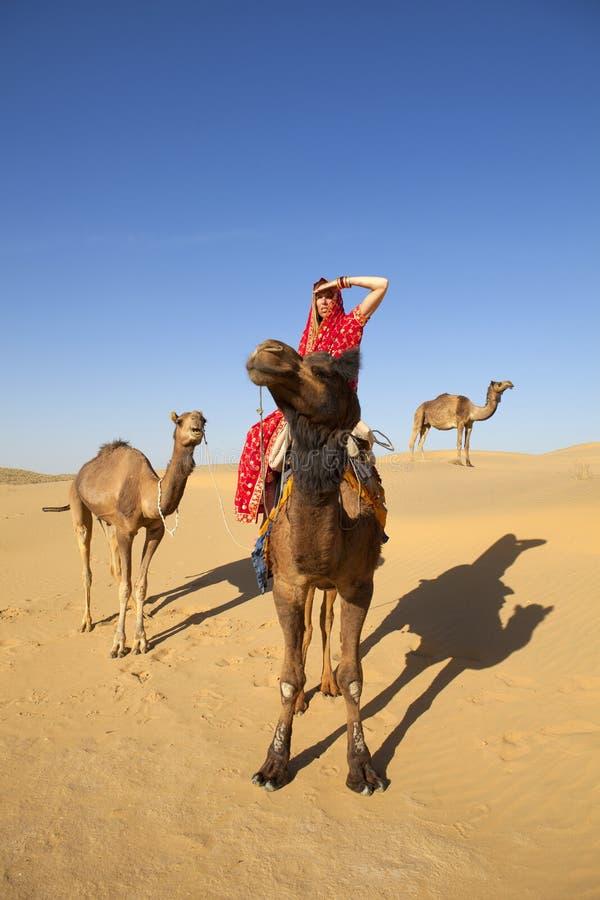 Woman in sari riding a camel.