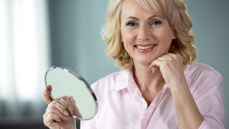 Woman satisfied with effect of new vitamin complex for skin beauty and freshness. Stock photo royalty free stock images