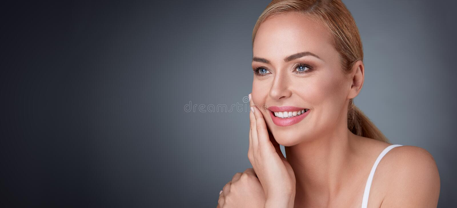 Woman satisfied with her nature beauty. Smiling middle aged woman satisfied with her nature beauty royalty free stock photos