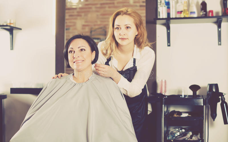 Woman is satisfied with work of young haircutter. And her hairdo in hairdress salon royalty free stock image