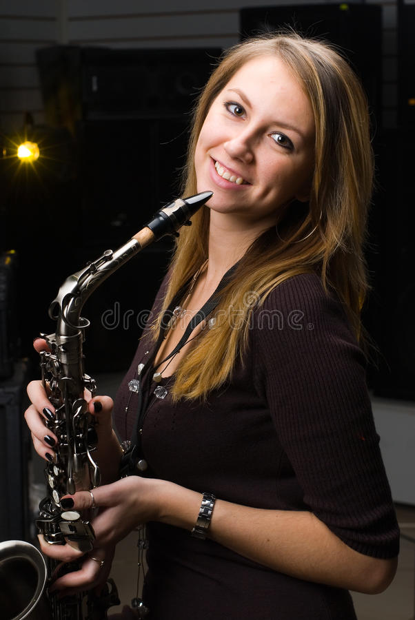 Woman with saxophone. At music concert stock image
