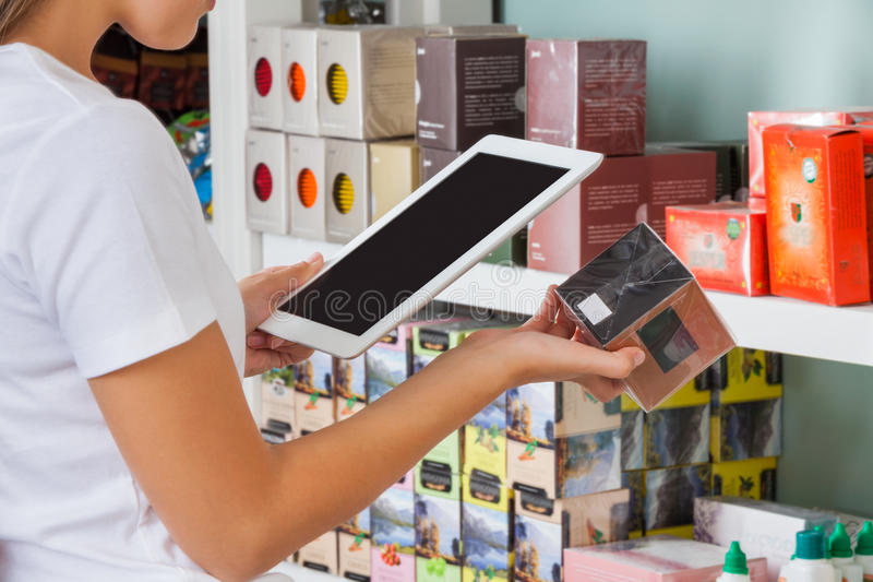 Woman Scanning Barcode Through Digital Tablet. Midsection of young woman scanning barcode through digital tablet at supermarket royalty free stock photo