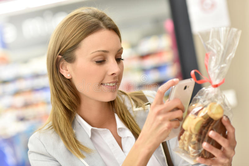 Woman scanning cookies for price. Woman customer scanning food products in grocery store royalty free stock photo
