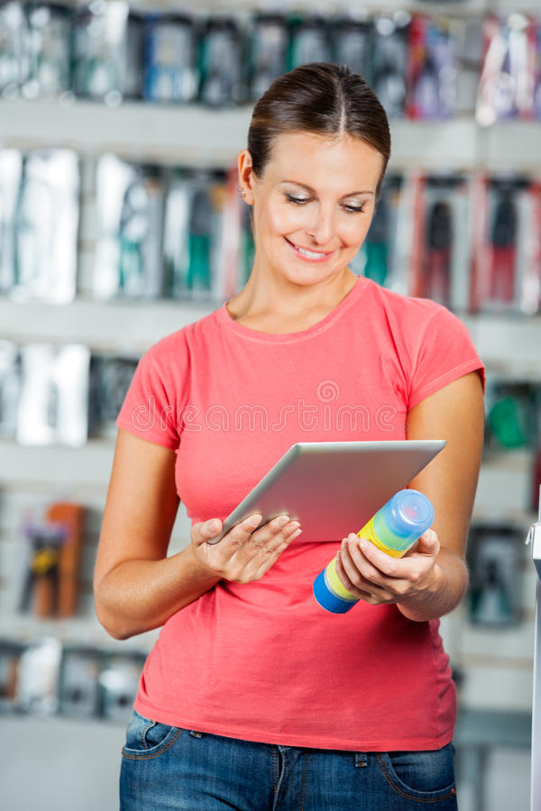 Woman Scanning Product Through Digital Tablet In. Beautiful mid adult woman scanning product's barcode through digital tablet in hardware store royalty free stock images