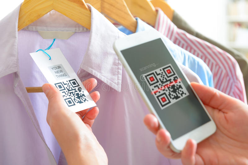 Woman scanning QR code. From a label in a shop with mobile phone royalty free stock photo