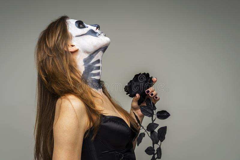 Woman with scary Halloween skeleton makeup holding black rose flower over gray background stock photos