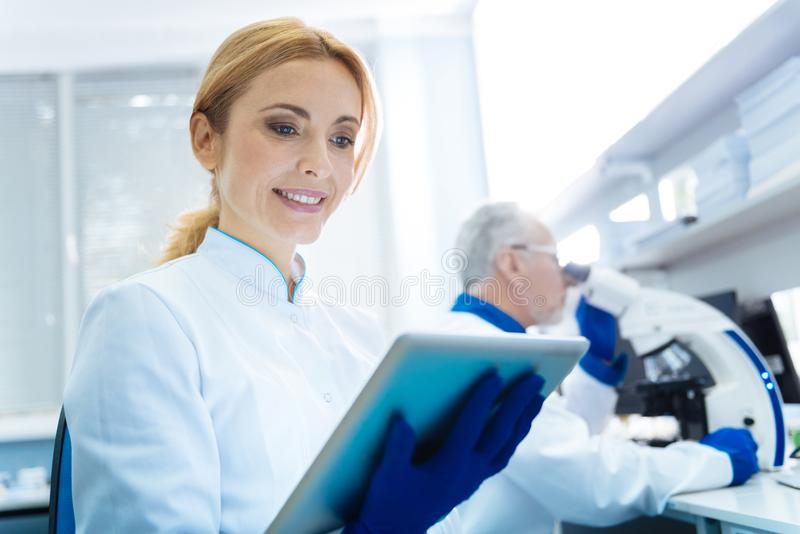 Happy smiling woman scientist in the lab. Woman of science. Attractive happy smiling budding women scientist wearing a uniform and holding a tablet while being stock images
