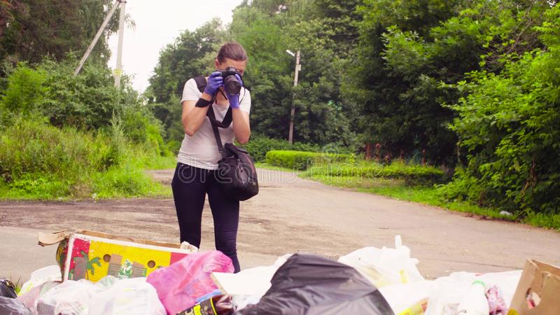 Scientist environmentalist making photos of garbage dump. royalty free stock image