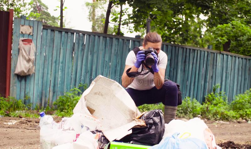 Scientist environmentalist making photos of garbage dump. stock photography