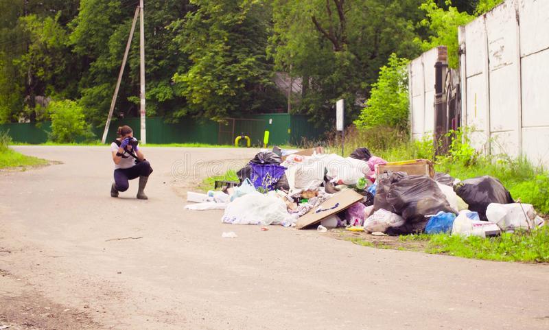 Scientist environmentalist making photos of garbage dump. Woman scientist environmentalist making photos of garbage dump stock images