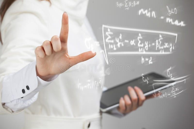Woman scientist or student working with various high school maths and science formula. Woman scientist or student working with various high school maths and stock image