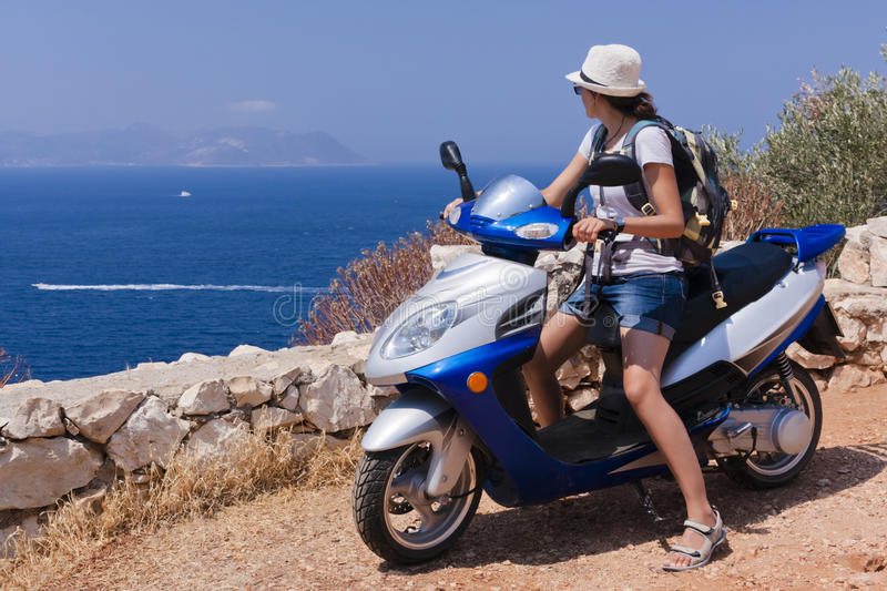 Woman on a Scooter. Young woman on a scooter is looking at the boats on blue Mediterranean sea royalty free stock image