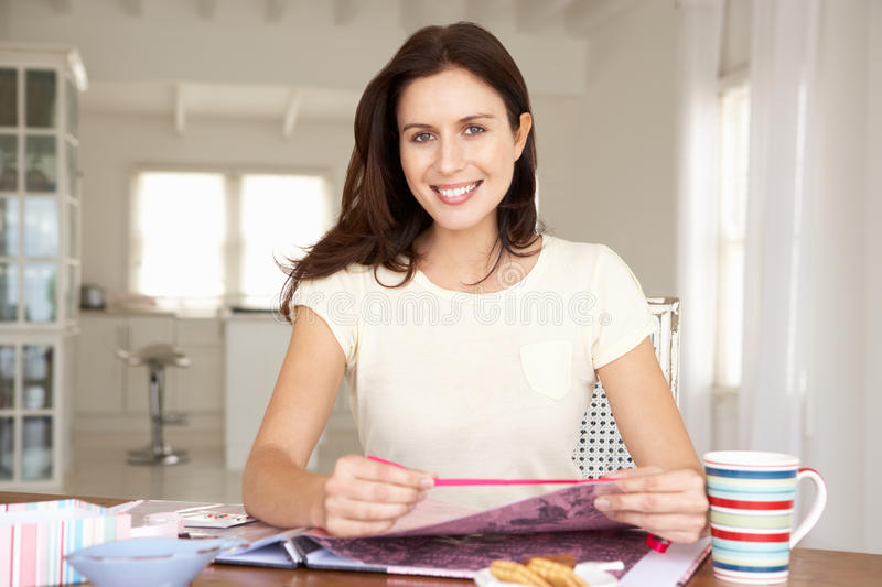 Woman scrapbooking at table stock images