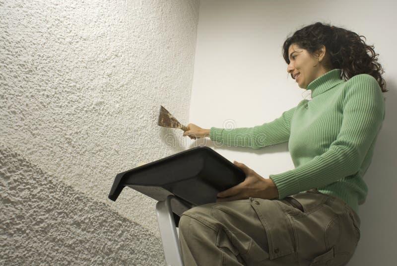 Woman Scrapes Wall - Horizontal royalty free stock photo