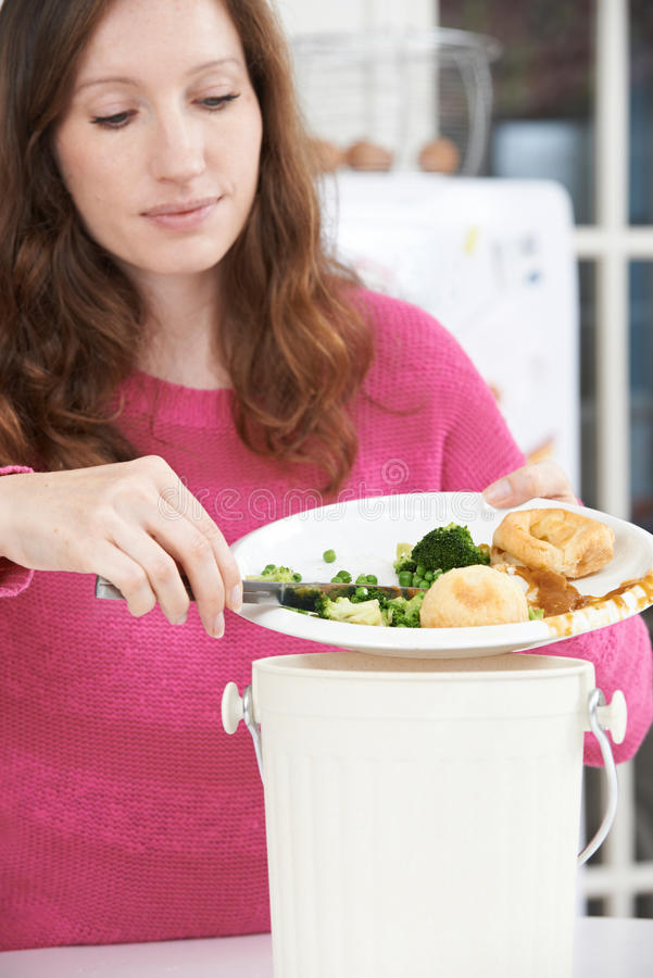 Woman Scraping Food Leftovers Into Garbage Bin stock photography