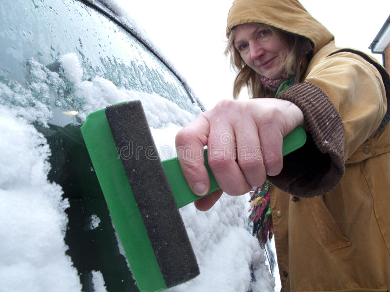 Woman scraping ice off car window stock photo
