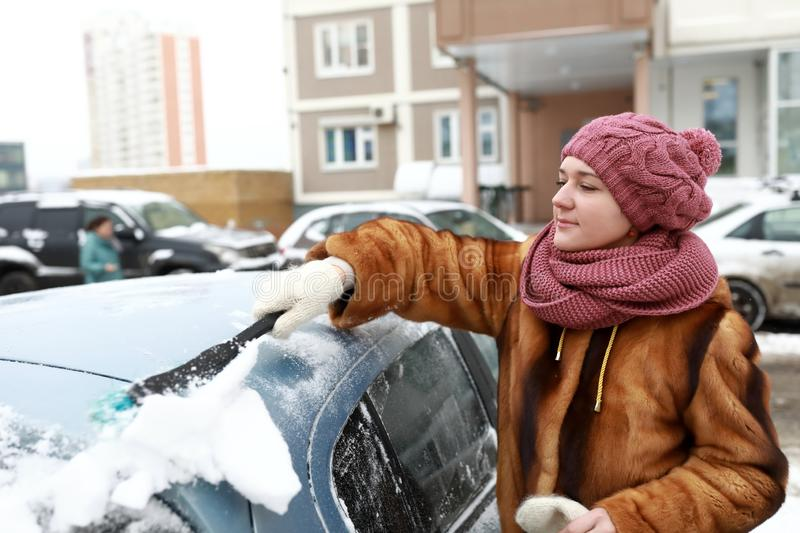 Woman scraping snow from car stock photos